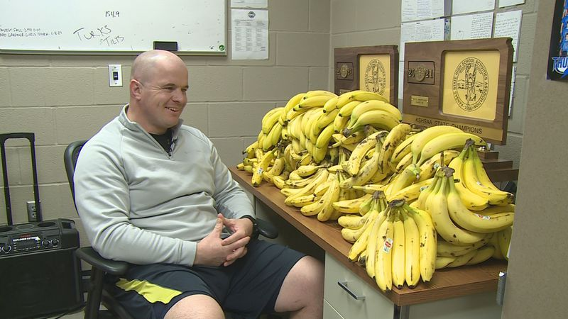 Washburn Rural wrestling coach Damon Parker sits at his desk, covered in roughly 600 bananas.