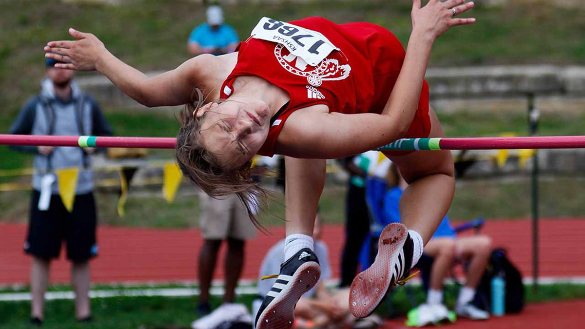 Wichita North's Riannon St. Clair goes over the bar in the high jump at the state track and...