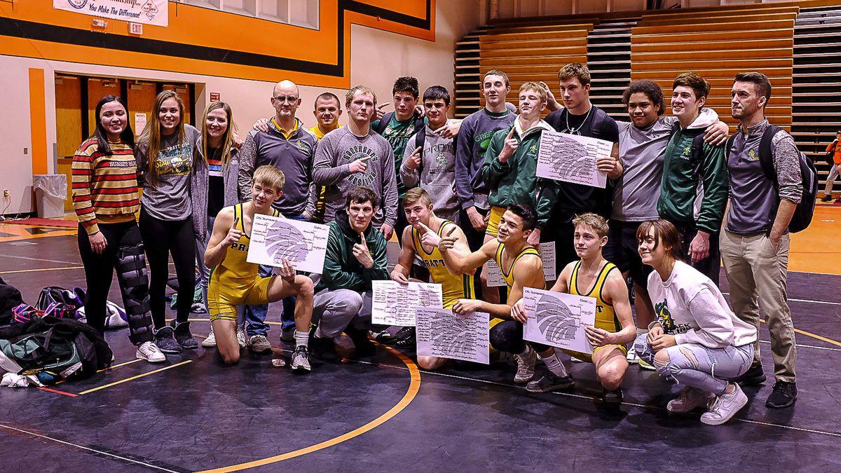 Members of the Pratt Greenback wrestling team hold up their brackets in celebration of winning...